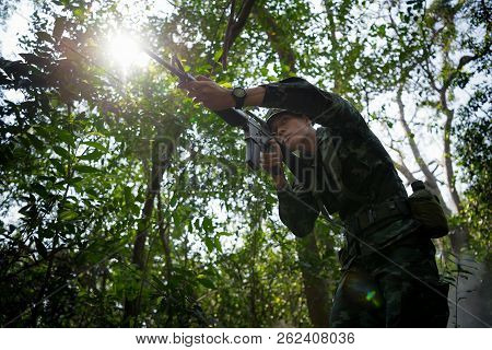 Silhouette Of Squad Soldiers Patrolling Across The Deep Forest Area.