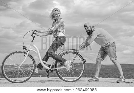 Teach Adult To Ride Bike. Man Helps Keep Balance And Ride Bike. Find Balance. Woman Rides Bicycle Sk