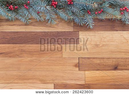 Christmas Wooden Background With Conifer Branch Decorated With Natural Red Barries.
