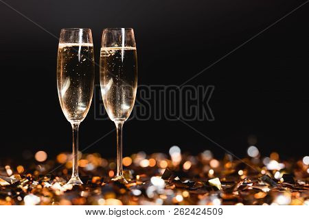 Champagne Glasses On Golden Confetti On Black For New Year Celebration