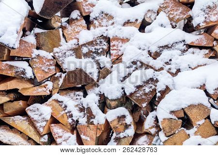 Winter Background Texture Pattern With Stacked Dry Chopped Firewood Logs Covered With Snow. Firewood
