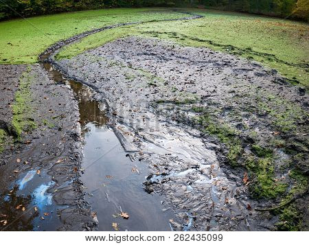 Contaminated Empty Pond With Oil And Mud.