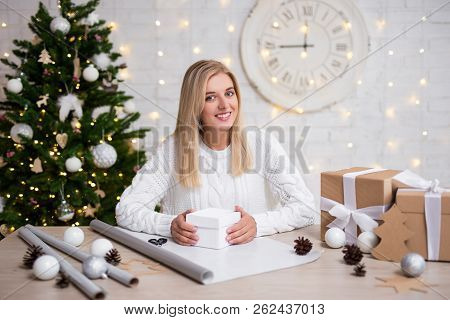 Young Woman Packing Christmas Gifts In Living Room