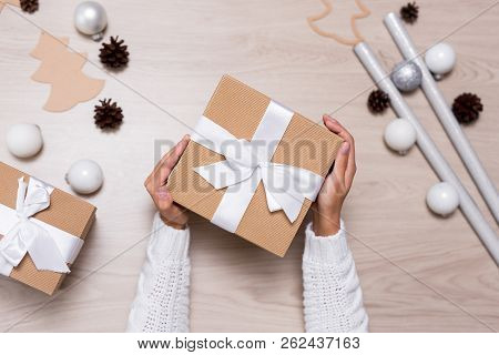 Top View Of Female Hands With Christmas Gift Over Wooden Table Background