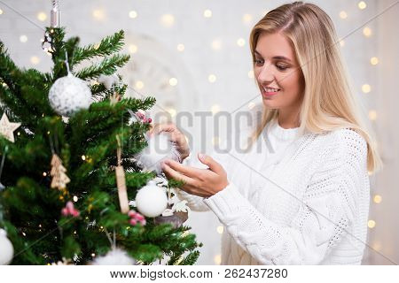Portrait Of Young Woman Decorating Christmas Tree At Home