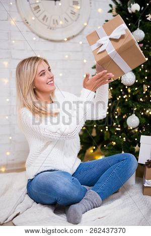 Portrait Of Young Happy Woman Sitting In Living Room With Decorated Christmas Tree And Gift Boxes