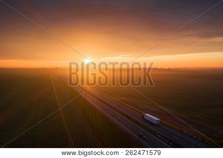 Truck On Highway In The Morning. Cargo Transportation Background. Aerial Transportation Landscape. C