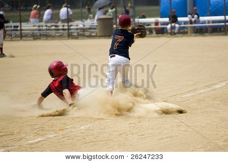 Little league baseball player sliding into third base
