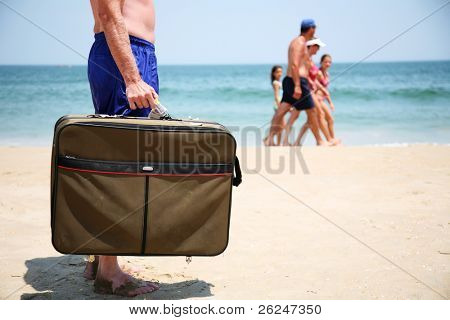 Man with a suitcase on the beach