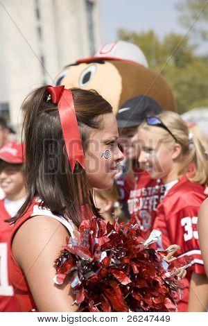 Ohio State University cheerleader with Brutus the Buckeye in the back ground