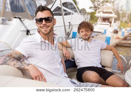 Two Friends Rest On A Yacht, On The River Bank, Near The Yacht Club