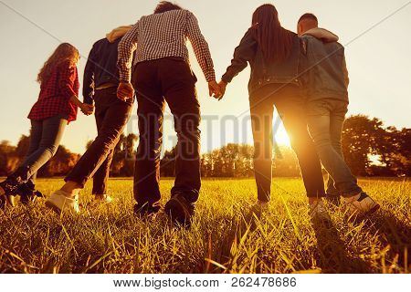 Back View. A Group Of Friends Holding Hands At Sunset In The Par