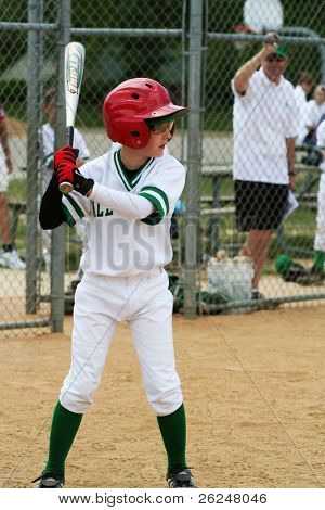 Little league baseball player swings at a pitch