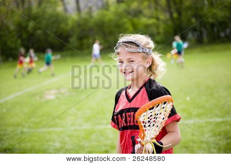 Lacrosse player with the game going on in the background