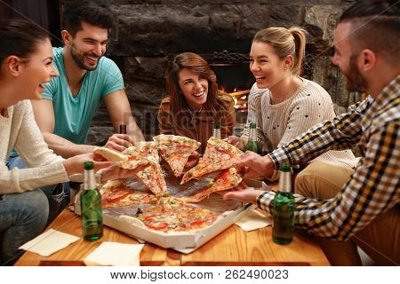 Group of young hungry people taking pieces of big family pizza