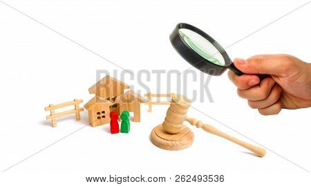 Magnifying Glass Is Looking At The Wooden Apartment House With People, Keys And A Judge Hammer On A