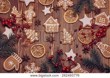 Christmas gingerbreads. Christmas decorations. Handmade cookies, fir branches with decorations on the wooden table. Top view.  Christmas and New Year treats.