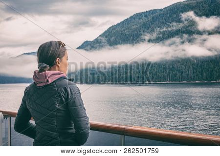 Alaska inside passage cruise tourist woman in Misty Fjords near Ketchikan, Alaskan famous landmark attraction. Scenic cruising in North America.