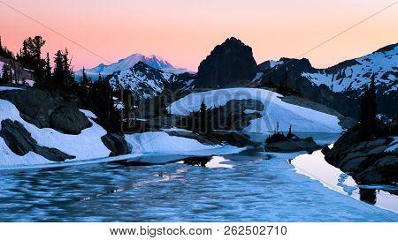 Sunrise Illuminates A Beautiful Image Of Mt. Rainier, Cathedral Peak And Frozen Robin Lake. Cascade