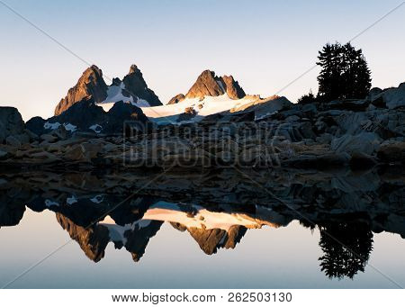 The Dramatic And Icy Peaks Of Chimney Rock And Overcoat Peak Reflected In The Mirror Waters Of Tank