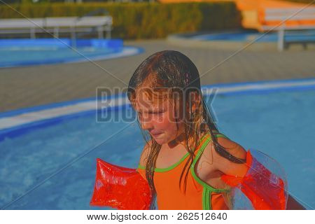 Happy Little Girl Enjoying Summer Day In The Swimming Pool. Cute Girl With Inflatable Armbands In Sm