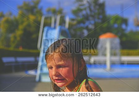 Happy Little Girl Enjoying Summer Day In The Swimming Pool. Cute Girl Shivering With Cold. Summer An