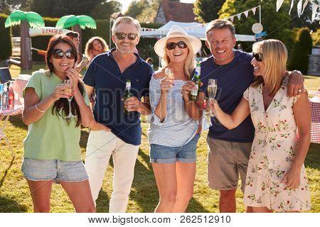 Portrait Of Mature Friends Enjoying Drinks At Summer Garden Fete