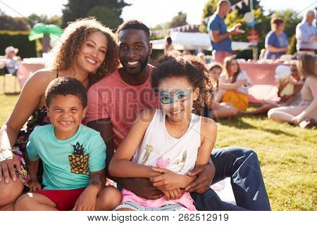 Portrait Of Family With Children Sitting On Rug At Summer Garden Fete