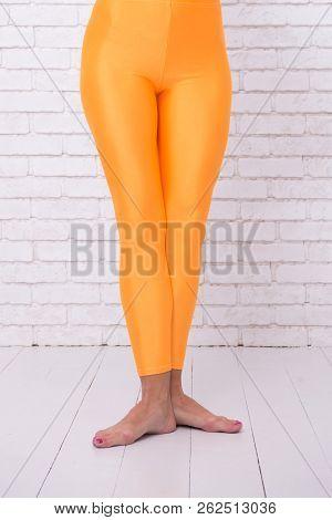 Dancing Ballet Position Of Feet. Orange. Practicing In Ballet Studio. Sport Wear Fashion. Woman In O