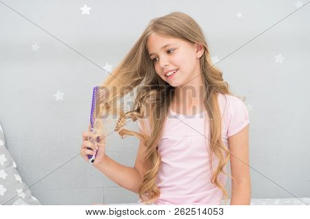 Child curly hairstyle hold hairbrush or comb. Apply oil before combing hair. Healthy hair. Conditioner or mask organic oil comb hair. Beauty salon tips. Girl long curly hair grey interior background. poster