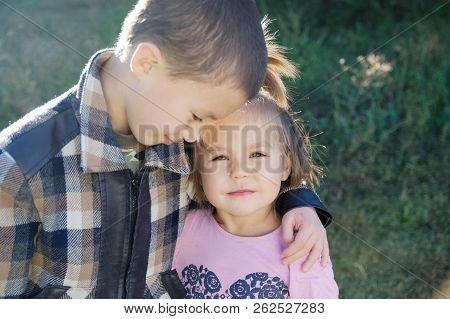 Boy And Little Girl Hugging Portrait. Happy Smiling Children Outdoors At Sunny Day.friendship Siblin