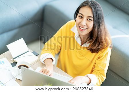 Young Attractive Happy Asian Female Student Sitting At Living Room Floor Smiling And Looking Up At C
