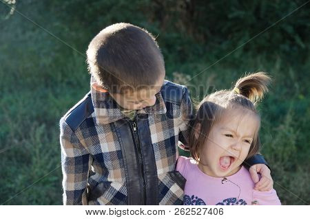 Boy And Funny Little Girl Hugging Portrait. Happy Smiling Children Outdoors At Sunny Day. Friendship