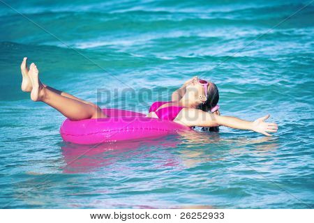 Funny woman relaxing on pink inner tube