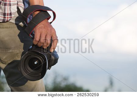 Photographer Holding His Camera. Travelers Hold A Dslr Camera On The Mountain.