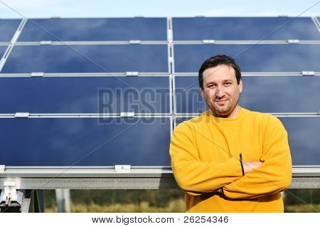 Young male engineer with solar panels in background