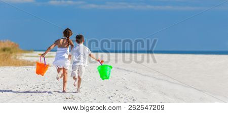 Panoramic web banner happy children, boy girl, brother and sister running and having fun playing in the sand on a beach with bucket and spade