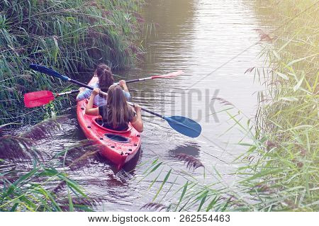 Children Swim Through A Narrow Channel Of The River In Kayaks. A Pair Of Children Go Kayaking On The