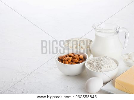 Fresh Dairy Products On White Table Background. Glass Jar Of Milk, Bowl Of Cottage Cheese And Baking