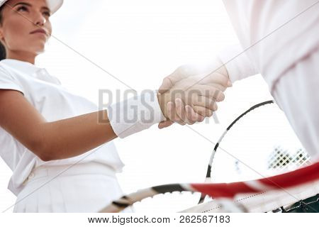 Shaking Hands After Good Game. Close-up Of Man And Woman In Wristband Shaking Hands Upon The Tennis