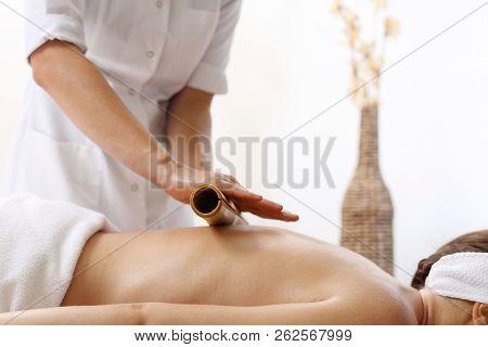 Bamboo Massage. The Masseur Massages The Body Using Bamboo Sticks.
