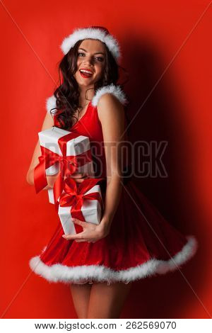 Pretty Pin-up style Santa girl in red hat and dress holding stack of gifts on red background