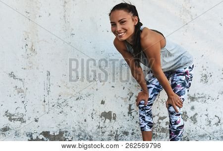 Young Smilng Woman During A Break Outdoors Against Concrete Wall. Happy Athletic Female Relaxing Aft