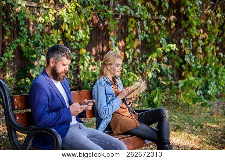 Man With Beard And Woman Read Alternative Information Storage. Read Book In Park Pleasant Leisure. I