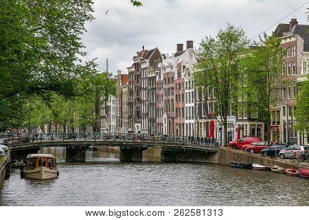 Amsterdam, Netherlands - June 25, 2017: Historical Buildings And The Bridge Gasthuisbrug On The Sing