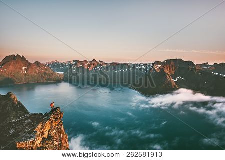 Travel Man Alone On The Edge Cliff In Mountains Above Fjord Hiking Adventure Lifestyle Extreme Vacat