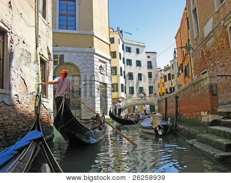 The gondoliers floats on the channel of Venice with tourists