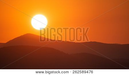 Sunset, sunrise over mountains silhouette. Golden sun on colorful sky background, space, panoramic view.