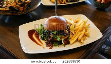 Fast food concept. Hamburger with french fries on white dish. Close up view, blur background.