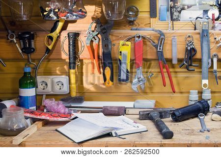 Wooden Workbench At Workshop. Lot Of Different Tools For Diy And Repair Works. Wood Messy Table With